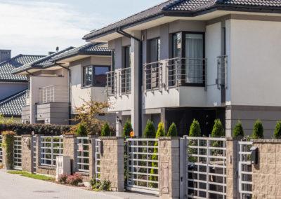 Trzy domy szeregowe Home Premium przy ulicy Szkolnej widziane pod kątem z ulicy.