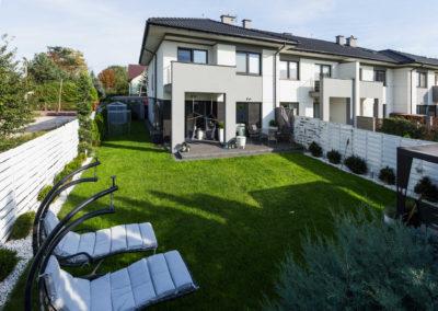 Segment narożny Home Premium przy ul. Szkolnej, widziany od strony obsianego trawą ogródka z białymi leżakami.