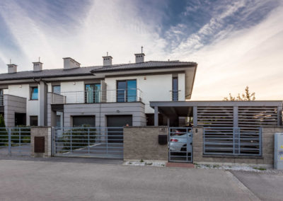 Segment narożny Home Premium wraz z zewnętrznym garażem przy ul. Szkolnej z białoniebieskim niebem..