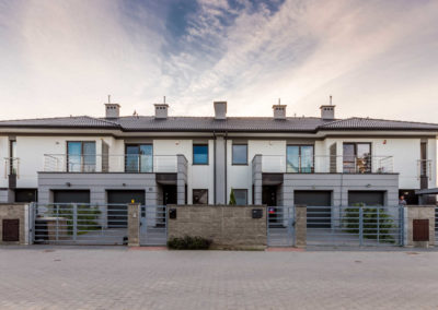 Przednia elewacji budynku szeregowego Home Premium przy ul. Szkolnej, z białoniebieskim niebem.