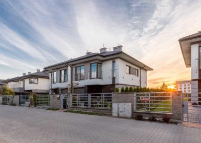 Trzy domy szeregowe Home Premium przy ulicy Szkolnej od przodu, o zachodzie słońca.