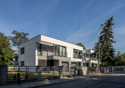 Szaro-biała elewacja dwóch domów szeregowych Home Premium, z płaskim dachem i o nowoczesnej bryle, przy ul. Dolnej w Łomiankach koło Warszawy, w słoneczny dzień.