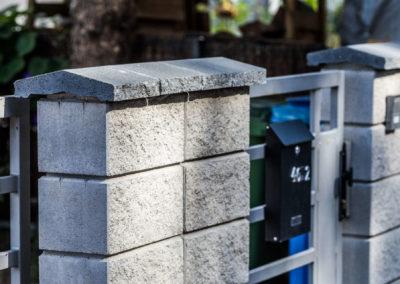 Fragment szarego, murowanego ogrodzenia i bramki ze skrzynką pocztową przy budynku Home Premium na ulicy Dolnej w Łomiankach.