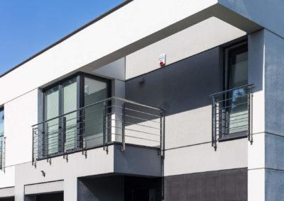 Taras i okno na pierwszym piętrze z nowoczesnym typem elewacji w jednym z segmentów Home Premium przy ul. Dolnej w Łomiankach.