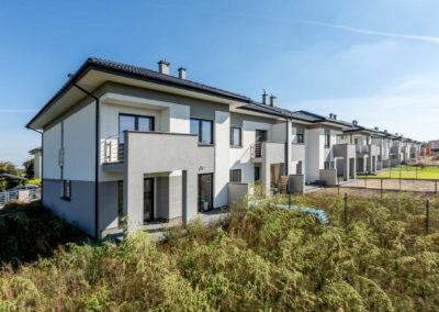 Szaro-biała elewacja szeregu domów Home Premium przy ul. Jutrzenki widziana od strony ogródka narożnego segmentu w słoneczny dzień.