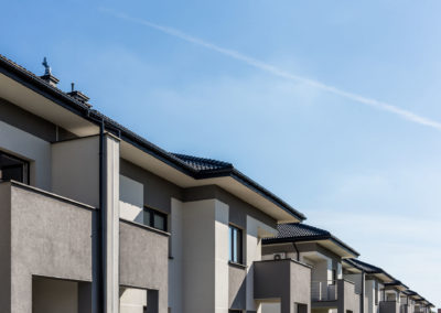 Fragment elewacji i dachu pokrytego ciemna dachówką segmentów przy ul. Szkolnej z błękitnym niebem.