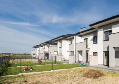 Ciąg nowych domów szeregowych Home Premium przy ul. Jutrzenki, widzianych z ogródka segmentu narożnego w słoneczny dzień.