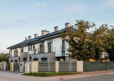 Budynek szeregowy Home Premium przy ul. Prostej widziany z naprzeciwka. W ogrodzie narożnego segmentu wysokie drzewa.