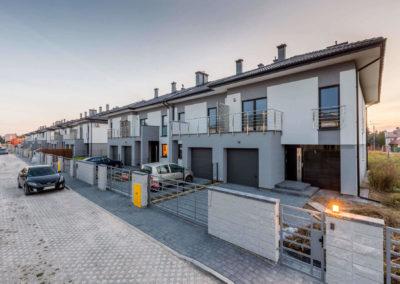 Szereg domów segmentowych Home Premium widzianych pod kątem z ulicy Jutrzenki, sprzed pierwszego narożnego segmentu.